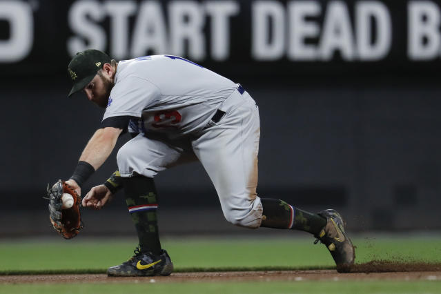 Los Angeles Dodgers third baseman Max Muncy fields a ground ball by Cincinnati Reds' Kyle Farmer before throwing Farmer out at first in the eighth inning of a baseball game, Friday, May 17, 2019, in Cincinnati. (AP Photo/John Minchillo)