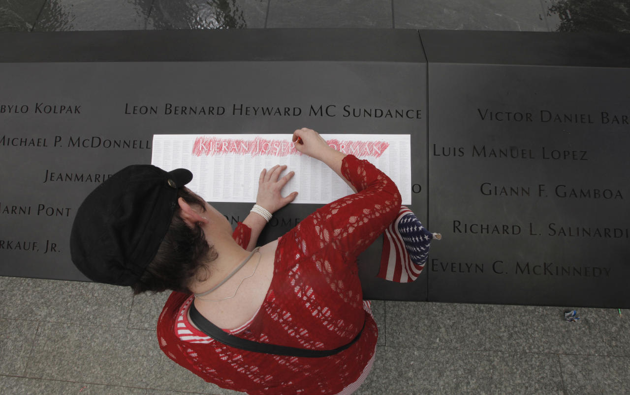 A woman makes an impression of one of the names on the wall at the Sept. 11 memorial, during the 10th anniversary observance of the terrorist attacks on the World Trade Center, Sunday, Sept. 11, 2011 in New York. (AP Photo/Lucas Jackson, Pool)
