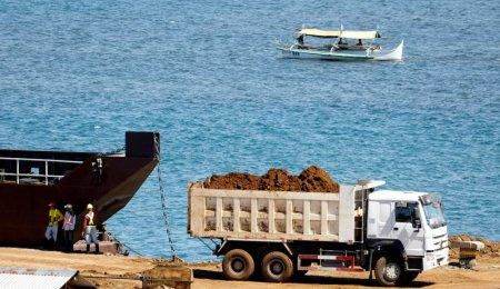 FILE PHOTO: A truck loads rocks and soil containing nickel-ore minerals into a barge in the mining town of Sta Cruz Zambales in northern Philippines February 8, 2017. REUTERS/Erik De Castro/File Photo