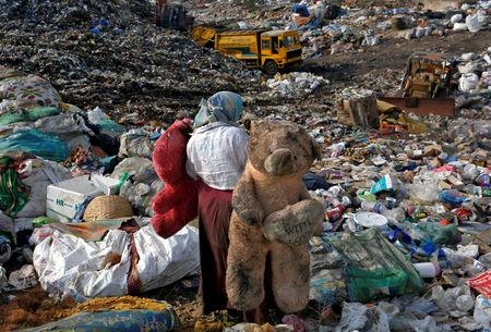 FILE PHOTO: A woman carries stuffed toys through a dump site on the outskirts of Mumbai, India, June 4, 2018. REUTERS/Francis Mascarenhas/File Photo