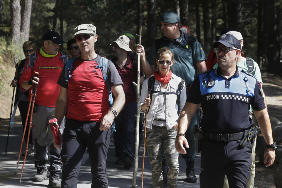Volunteers walks with a civil guard and a police officer after searching in woodland area in Cercedilla, just outside of Madrid, Spain, Tuesday, Sept. 3, 2019. A search squad of hundreds is combing a mountainous area outside Madrid 11 days after former alpine ski racer and Olympic medalist Blanca Fernandez Ochoa went missing.(AP Photo/Paul White)