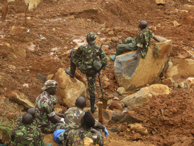 <p>Security forces take a rest after searching for bodies from the scene of heavy flooding and mudslides in Regent, just outside of Sierra Leone's capital Freetown. Aug. 15 , 2017. (Photo: Manika Kamara/AP) </p>