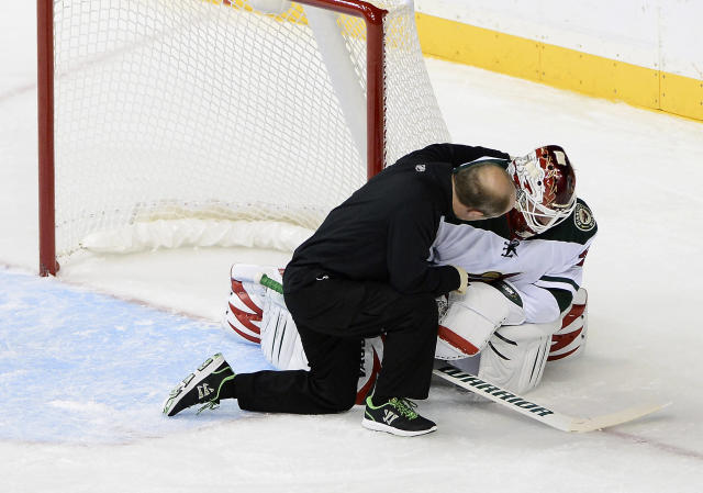 Minnesota Wild goalie Niklas Backstrom, right, of Finland, is attended to after colliding with Nashville Predators forward Eric Nystrom and was taken out of the game in the first period of an NHL hockey game on Tuesday, Oct. 8, 2013, in Nashville, Tenn. (AP Photo/Mark Zaleski)