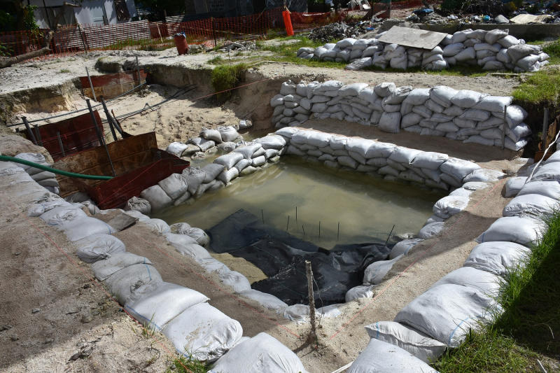 This June 1, 2019 photo provided by History Flight shows graves of U.S. servicemen under the water table in Tarawa, Kiribati. A nonprofit organization that searches for the remains of U.S. servicemen lost in past conflicts has found what officials believe are the graves of more than 30 Marines and sailors killed in one of the bloodiest battles of World War II. (Eric Albertson/Defense POW/MIA Accounting Agency/History Flight via AP)