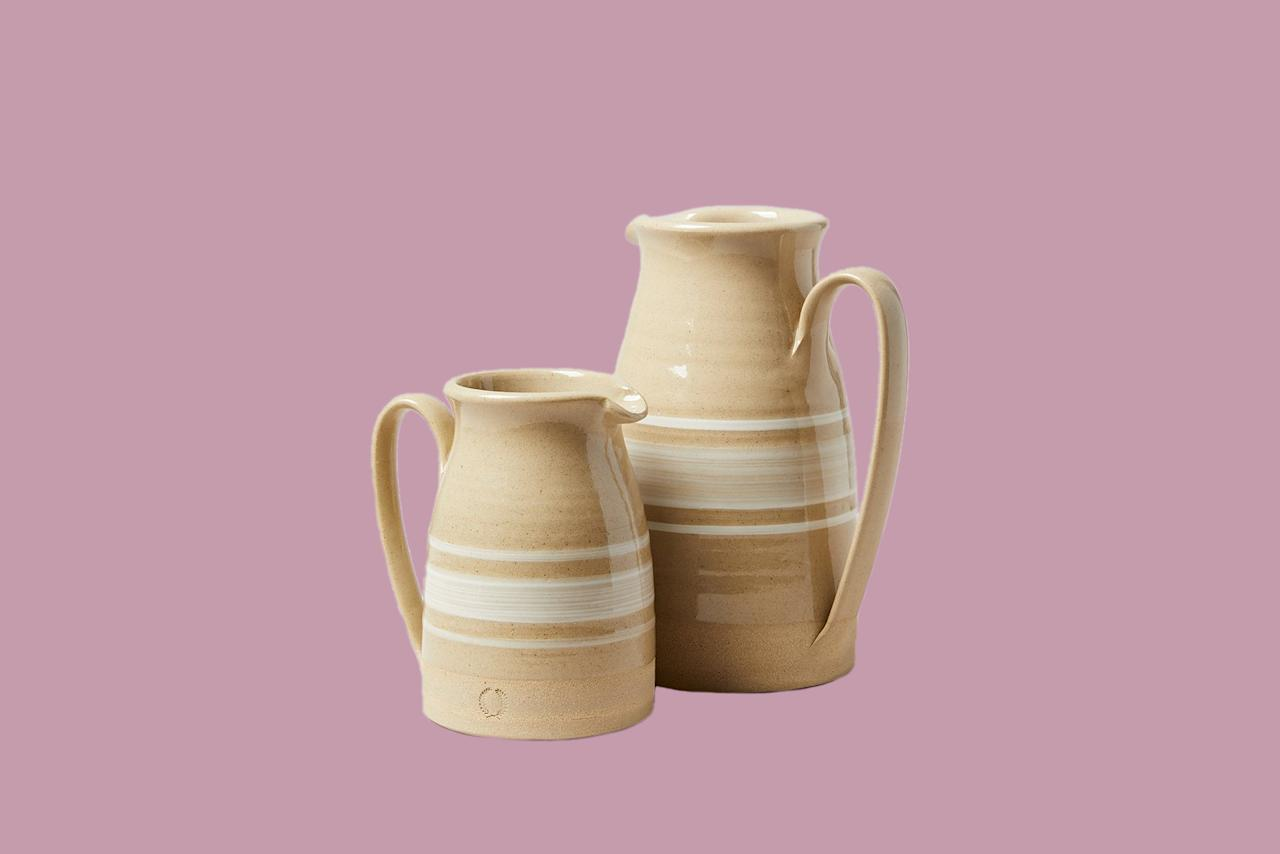 """<p>Fill these banded pitchers with flowers on a console or coffee table, use them for iced tea in the summer, or just set them on a shelf to be admired. After all, nothing says cabin quite like handmade pottery.</p> <p><em><strong>Shop Now</strong>: Farmhouse Pottery Yellowware Pitcher, from $165, <a href=""""http://www.anrdoezrs.net/links/9104911/type/dlg/sid/MSLHOMECabinInspiredDecorHBDec19/https://food52.com/shop/products/3287-yellowware-pitcher"""">food52.com</a>.</em></p>"""