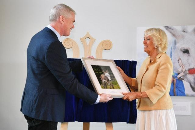 Chief executive officer of The Donkey Sanctuary Mike Baker presents the Duchess of Cornwall with a birthday gift during her visit