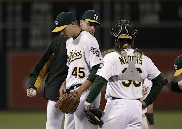 Oakland Athletics pitcher Jim Johnson (45) is relieved by manager Bob Melvin, rear, during the ninth inning of a baseball game against the Cleveland Indians in Oakland, Calif., Wednesday, April 2, 2014. The Indians won 6-4. Johnson was the losing pitcher. In front is Athletics catcher Derek Norris. (AP Photo/Jeff Chiu)