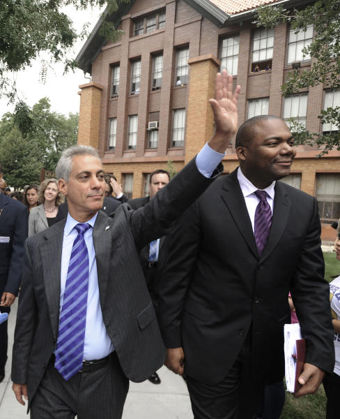 FILE - In this Sept. 9, 2011 file photo, Chicago Mayor Rahm Emanuel, left, and Chicago Public Schools CEO Jean-Claude Brizard greet students as they arrive at Carl Schurz High School in Chicago. Angered by Emanuel's call for a longer school day and wage and benefit concessions, 25,000 Chicago teachers began voting Wednesday, June 6, 2012, to consider authorizing their first strike in a quarter-century. (AP Photo/Paul Beaty, File)