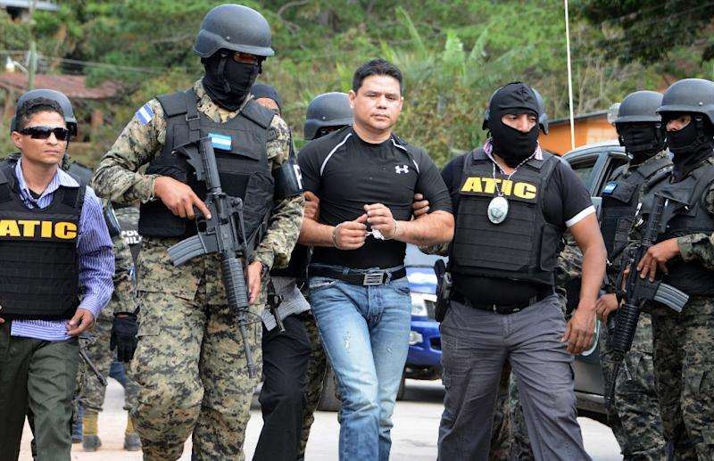 Members of the Honduran Military Police and of the Technical Agency of Criminal Investigation capture former National Police captain Alvaro Ernesto Garcia Calderon (C) in Valle de Angeles municipality, near Tegucigalpa on February 23, 2016