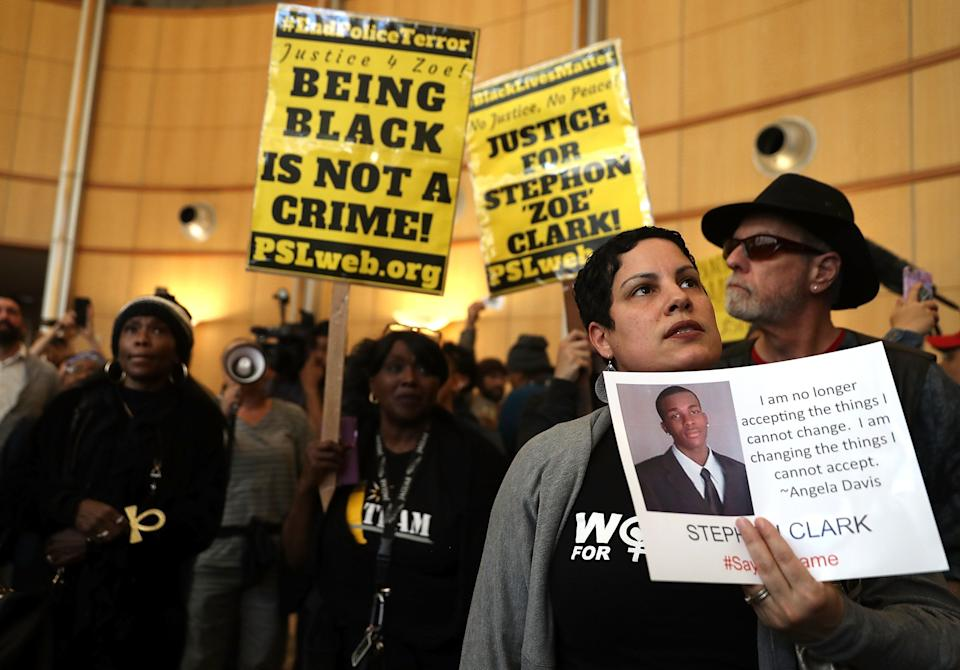 A protester holds a photo of Stephon Clark during a Black Lives Matter demonstration outside of Sacramento City Hall.