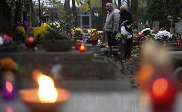 <p>People stop in front of a grave at the Powazki cemetery in Warsaw, Poland, Wednesday, Nov. 1, 2017. Candles and flowers cover tombstones in graveyards across Poland on All Saints' Day, as people honor the saints and their departed friends and family, in Christian tradition. (Photo: Alik Keplicz/AP) </p>