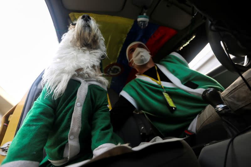 Nicolas Walteros, 52, sits inside a taxi with his dog Colonel using Santa's hats, amid the spread of the coronavirus disease (COVID-19) pandemic in Bogota