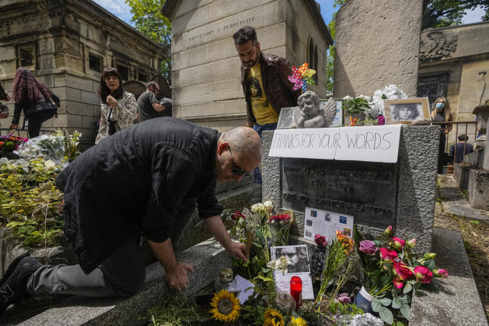 Fans gather at the tomb of rock singer Jim Morrison at the Pere-Lachaise cemetery in Paris, Saturday, July 3, 2021. Fans across Europe gathered at the grave of rock legend Jim Morrison to mark the 50th anniversary of his death.(AP Photo/Michel Euler)