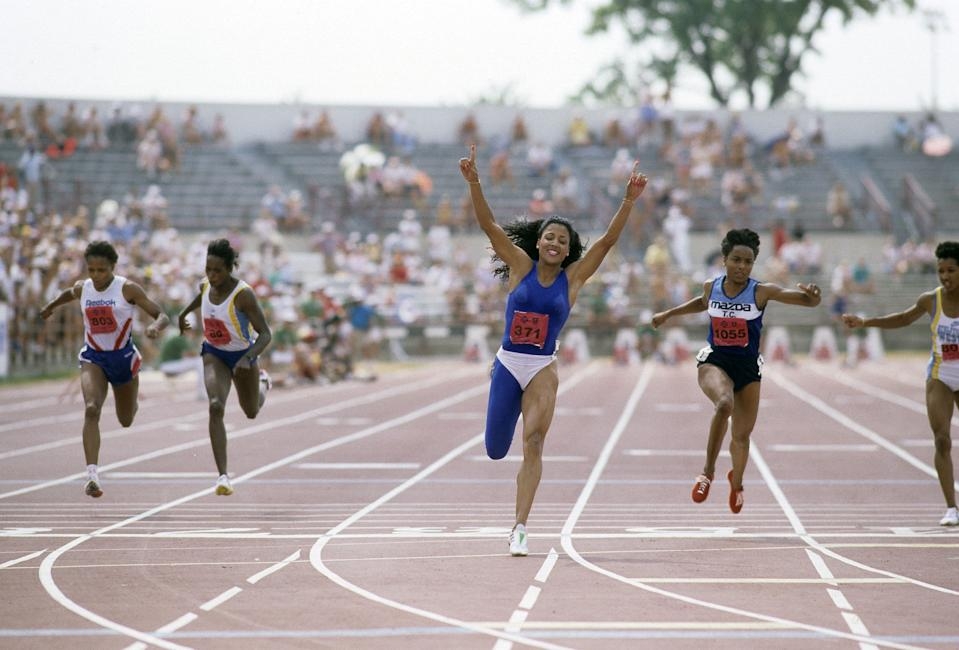 INDIANAPOLIS, IN - JULY 1988: Florence Griffith Joyner raises her fist after crossing the finish line first, competes during the 100m at the 1988 US Track and Field Olympic Trials in Indianapolis, Indiana. (Photo by Focus On Sport/Getty Images)