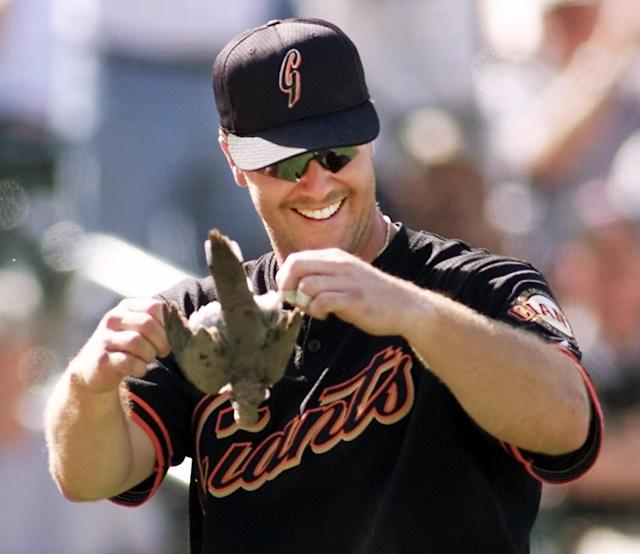The San Francisco Giants' Jeff Kent holds up a bird that was killed when it flew into the path of a pitch thrown by Arizona Diamondbacks ace Randy Johnson. (AP Photo/Ted S. Warren)