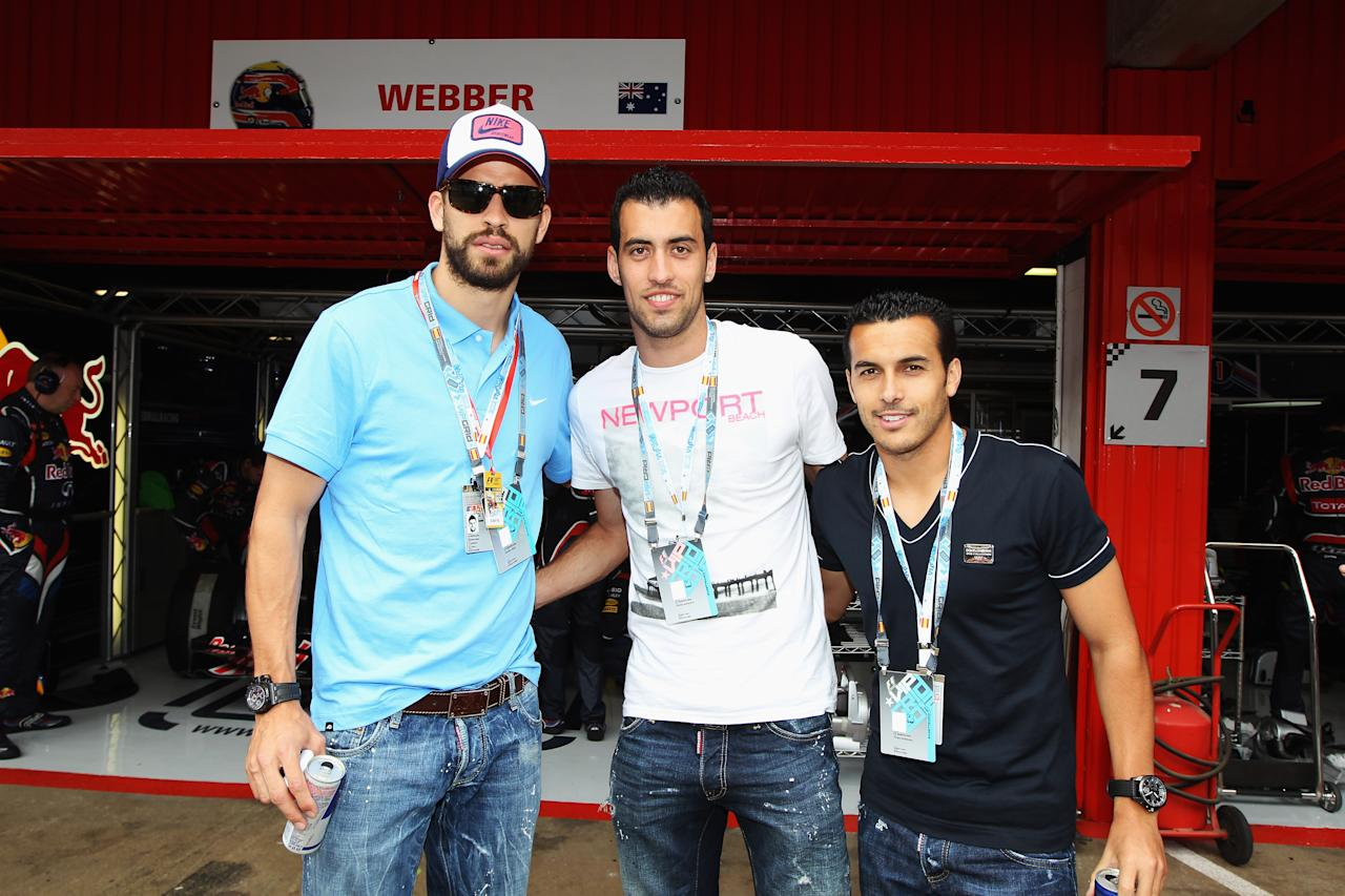 BARCELONA, SPAIN - MAY 13:  FC Barcelona players Gerard Pique (L), Sergio Busquets (C) and Pedro Rodriguez (R) are seen in the Red Bull Racing garage before the Spanish Formula One Grand Prix at the Circuit de Catalunya on May 13, 2012 in Barcelona, Spain.  (Photo by Mark Thompson/Getty Images)