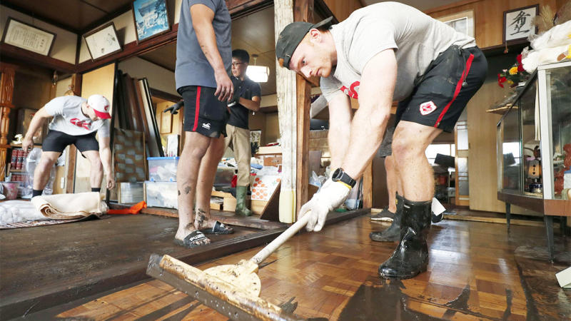 Canada's rugby player Nelson mops up some mud inside a house in Kamaishi after Typhoon Hagibis hit the community.