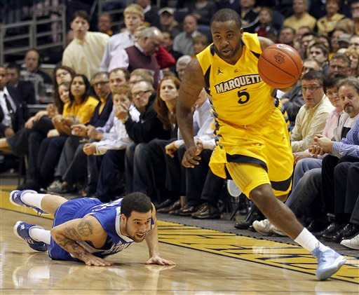 Marquette's Junior Cadougan (5) dribbles upcourt after stealing the ball from Seton Hall's Freddie Wilson, left, during the first half of an NCAA college basketball game, Tuesday, Jan. 31, 2012, in Milwaukee. (AP Photo/Jeffrey Phelps)
