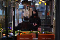 A waitperson wears a face mask while tending to a patron sitting in the outdoor patio of a sushi restaurant, late Monday, Dec. 28, 2020, in downtown Denver. (AP Photo/David Zalubowski)