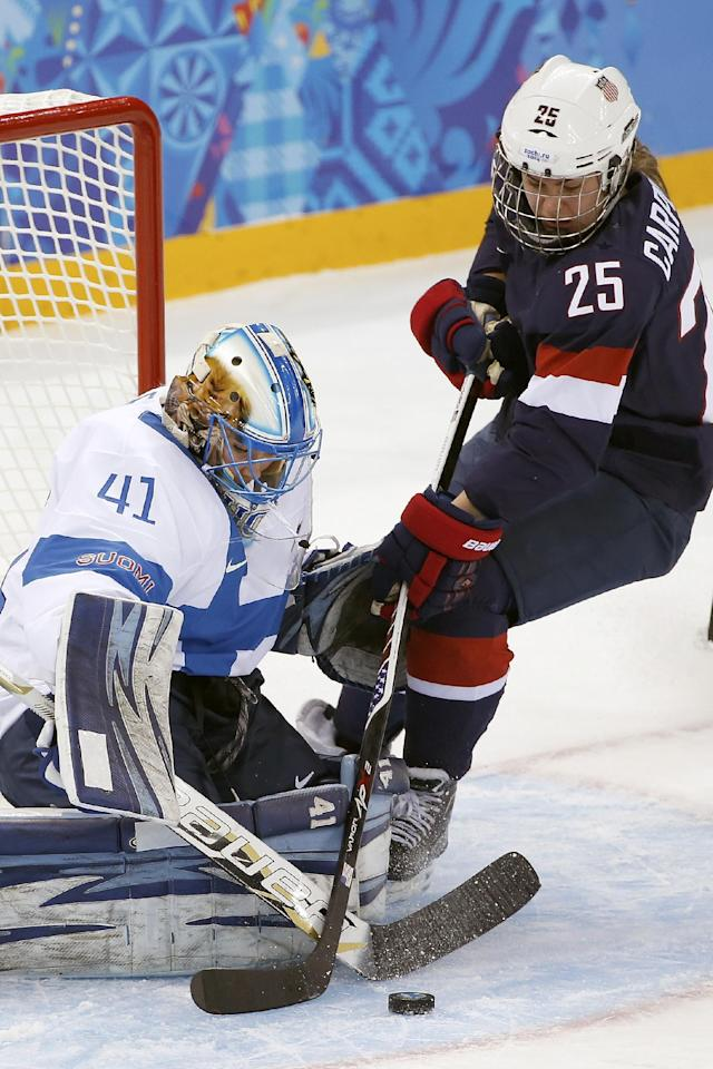 Goalkeeper Noora Raty of Finland blocks Alex Carpenter of the Untied States shot at the goal during the first period of the women's ice hockey game at the Shayba Arena during the 2014 Winter Olympics, Saturday, Feb. 8, 2014, in Sochi, Russia. (AP Photo/Petr David Josek)
