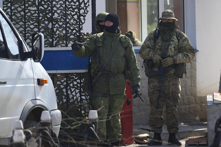 Pro-Russian soldiers check the traffic entering the Ukrainian navy headquarters, after taking control Wednesday, in Sevastopol, Crimea, on Thursday, March 20, 2014. Pro-Russian forces seized three Ukrainian warships Thursday and Ukraine said its troops were being threatened in Crimea as the U.S. announced a new round of sanctions against Russia for its annexation of the Black Sea peninsula. (AP Photo/Ivan Sekretarev)