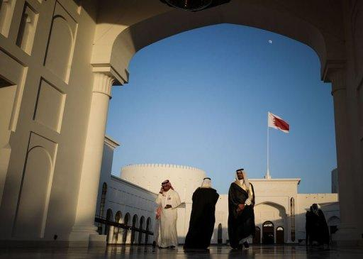 Men walk along the corridor at the Sakhir Palace in Manama, on December 24, 2012, as delegates attend the GCC summit