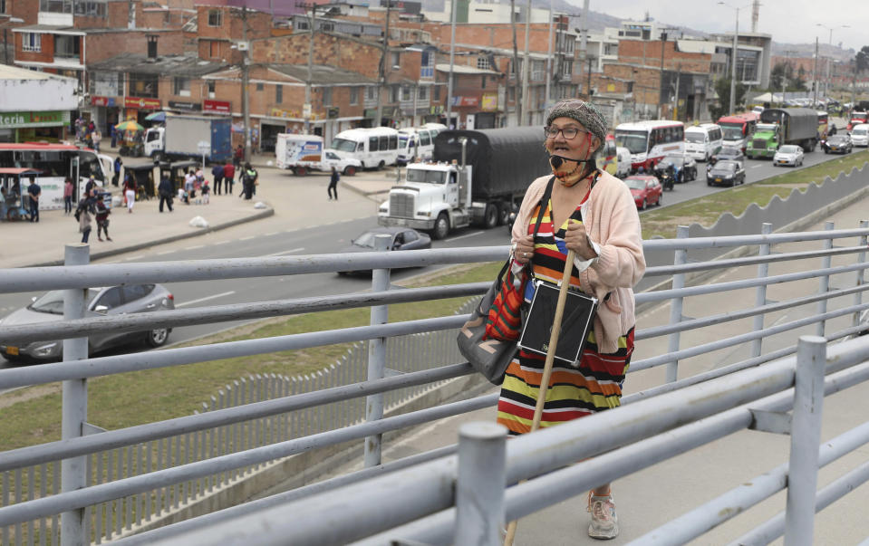 """Marlene Alfonso, a 69-year-old Venezuelan grandmother who goes by """"Toothless Cindy,"""" walks up the ramp to enter the Transmilenio, the crowded and crime-ridden public bus system in Bogota, Colombia, Tuesday, Nov. 3, 2020. Alfonso says that she was already performing for tips in her hometown of Caracas, long before she arrived in Bogota, home to more than 350,000 Venezuelans. (AP Photo/Fernando Vergara)"""