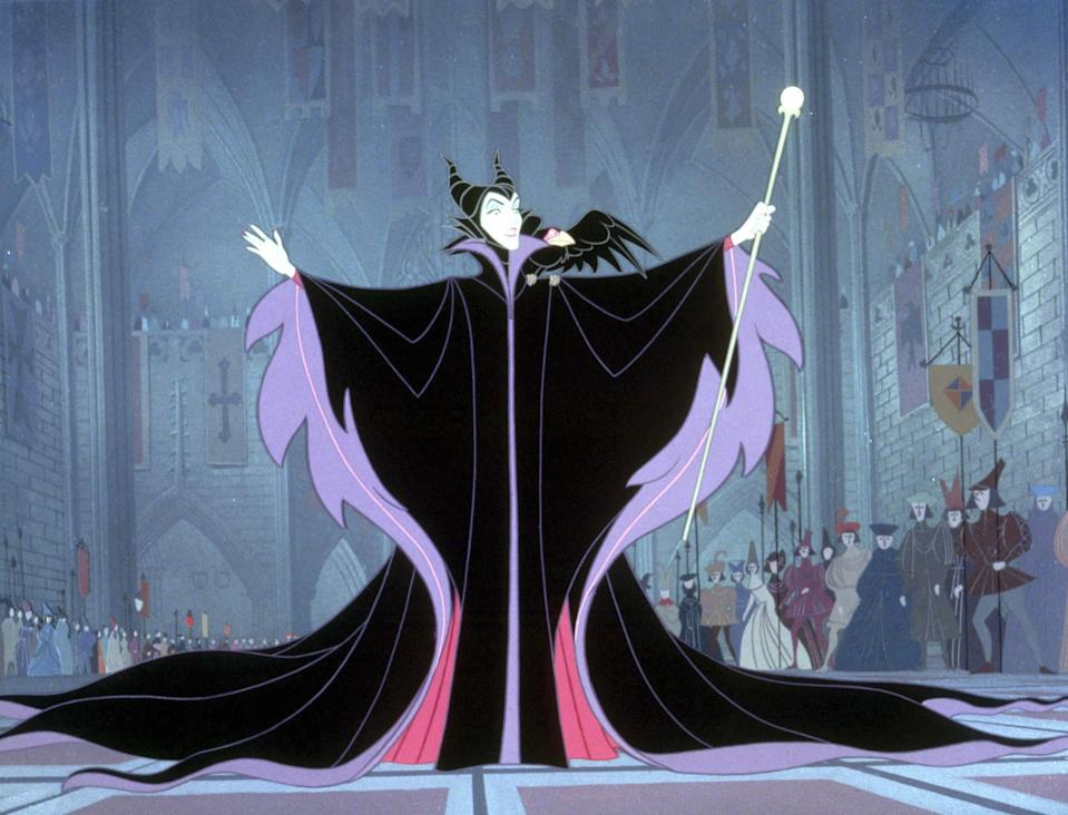 Maleficent showing up in a great hall with a massive cape and scepter