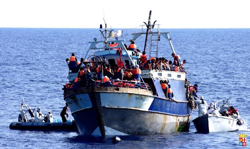 A handout picture released by the Italian Navy on August 4, 2014 shows migrants on a boat on the Mediterranean Sea after being rescued
