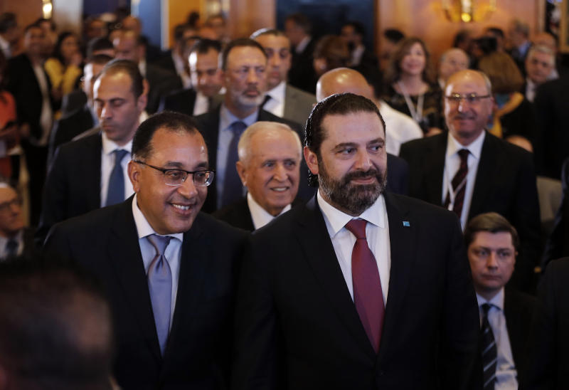 Lebanese Prime Minister Saad Hariri, right, and his Egyptian counterpart Mostafa Madbouly, left, arrive to attend the opening session of the Arab Economic Forum in Beirut, Lebanon, Thursday, May 2, 2019. The forum is taking place amid an economic crisis in Lebanon, which is suffering from slow growth, a high budget deficit and massive debt. The Lebanese government is holding open-ended sessions to discuss to approve the country's draft austerity budget. (AP Photo/Bilal Hussein)