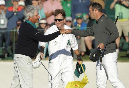 Fred Couples of the U.S. (L) taps fists with Paul Casey of England after they finished their second round play on the 18th green during the 2017 Masters golf tournament at Augusta National Golf Club in Augusta, Georgia, U.S., April 7, 2017. REUTERS/Mike Segar