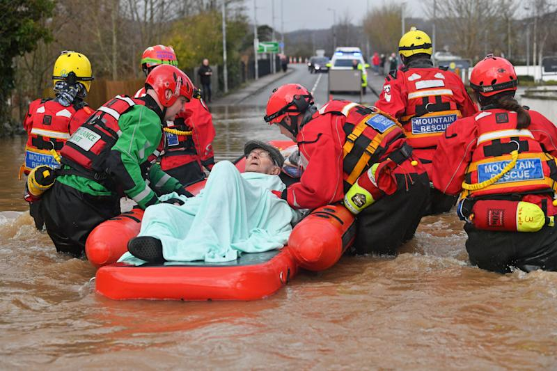 Mountain Rescue team members rescue Peter Morgan from his house where he has lived his whole life, which has been flooded in Monmouth. (Photo: PA)