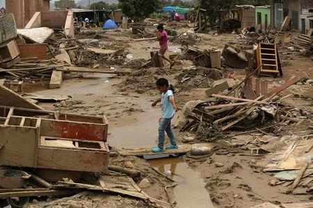 Residents walk on a flooded street, after rivers breached their banks due to torrential rains, causing flooding and widespread destruction in Huachipa, Lima