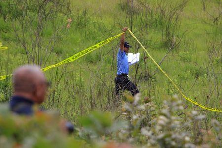 FILE PHOTO: A police officer cordons off a clandestine cemetery that was recently discovered in El Lolo neighbourhood, on the outskirts of Tegucigalpa, Honduras, July 21, 2017. REUTERS/Jorge Cabrera/File Photo