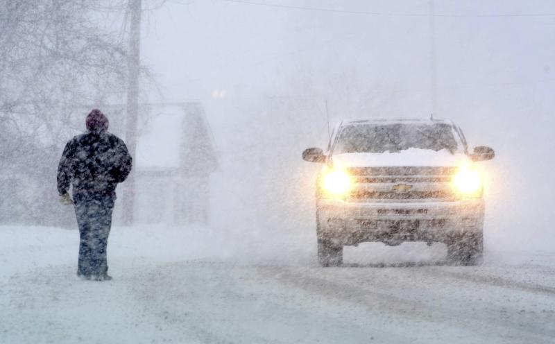 A pedestrian shares the road with motorists as he walks along State Road in North Adams, Mass., during a winter storm which brought blizzard conditions and heavy snow to the region, Sunday, Feb. 12, 2017. (Gillian Jones/The Berkshire Eagle via AP)