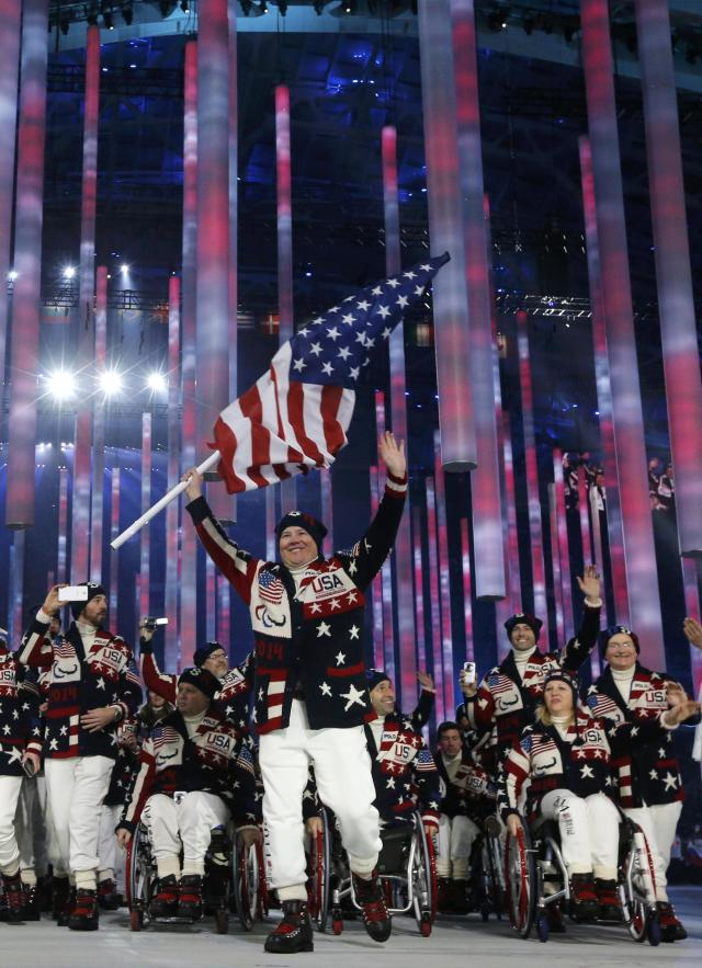 Flag-bearer Jonathan Lujan of the U.S. (C), leads his country's contingent during the opening ceremony of the 2014 Paralympic Winter Games in Sochi, March 7, 2014. REUTERS/Alexander Demianchuk (RUSSIA - Tags: OLYMPICS SPORT)