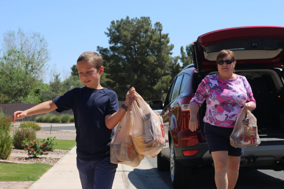 Dylan Pfeifer carries bags of canned and boxed food donated to his food drive from his grandmother Janice McGrew on Saturday, April 3, 2021, in Chandler, Ariz. Pfeifer hosted his third food drive since October in response to the coronavirus pandemic from his home. Each drive is the culmination of hours of work that involves drawing posters, going door-to-door to hand out flyers and working with his mother to post information on Facebook. (AP Photo/Cheyanne Mumphrey)