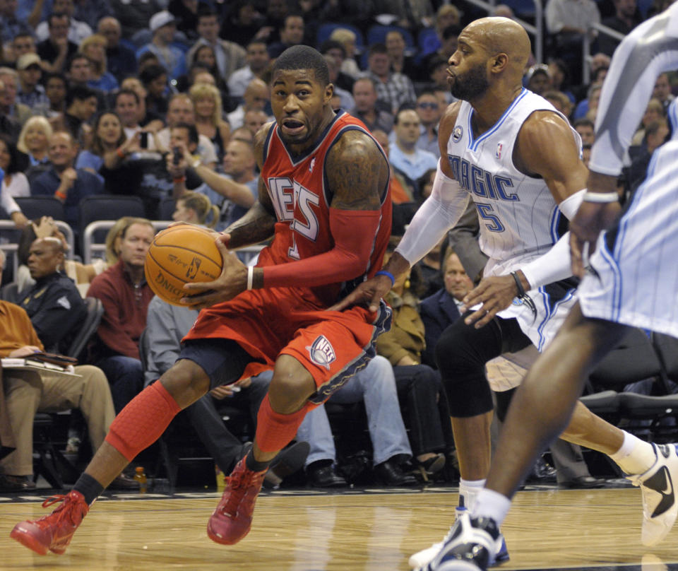 FILE - New Jersey Nets guard Terrence Williams, left, drives past Orlando Magic guard Vince Carter during the first half of an NBA basketball game in Orlando, Fla., in this Friday, Nov. 5, 2010, file photo. Eighteen former NBA players, including Williams, have been arrested on charges alleging they defrauded the league's health and welfare benefit plan out of about $4 million, according to an indictment Thursday, Oct. 7, 2021. (AP Photo/Phelan M. Ebenhack, File)