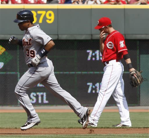 Detroit Tigers' Ramon Santiago (39) runs the bases past Cincinnati Reds shortstop Zack Cozart, right, after Santiago hit a solo home run during the second inning of a baseball game, Saturday, June 9, 2012, in Cincinnati. (AP Photo/David Kohl)
