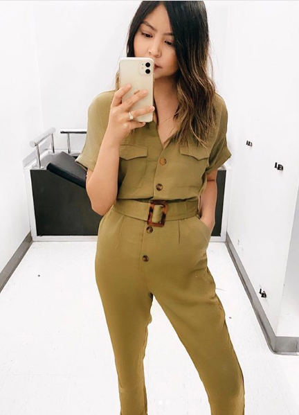 Woman taking a photo in a Kmart fitting room in a Kmart jumpsuit