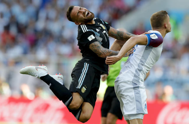 <p>Argentina's Nicolas Otamendi, left, takes a hit as Iceland's Alfred Finnbogason looks on </p>
