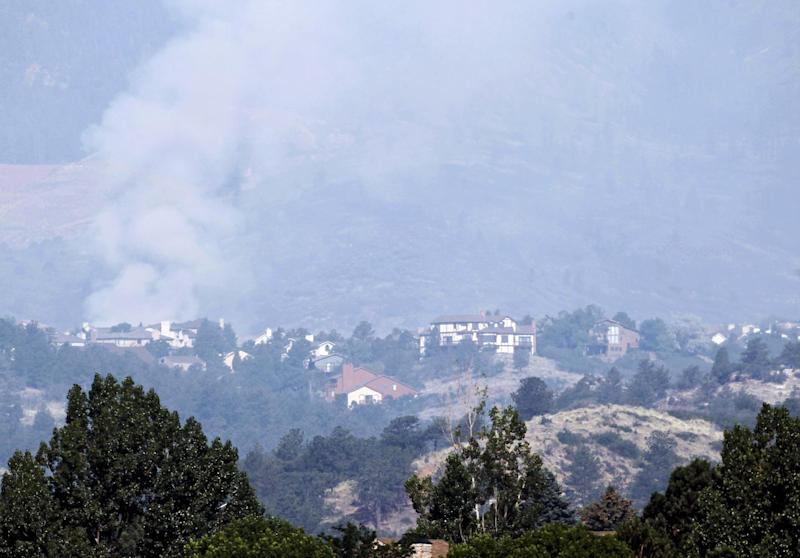 A plume of smoke from the Waldo Canyon wildfire rises behind homes west of Colorado Springs, Colo., Wednesday, June 27, 2012. A large number of homes were destroyed by the fire Tuesday night in subdivisions west of Colorado Springs. (AP Photo/Ed Andrieski)