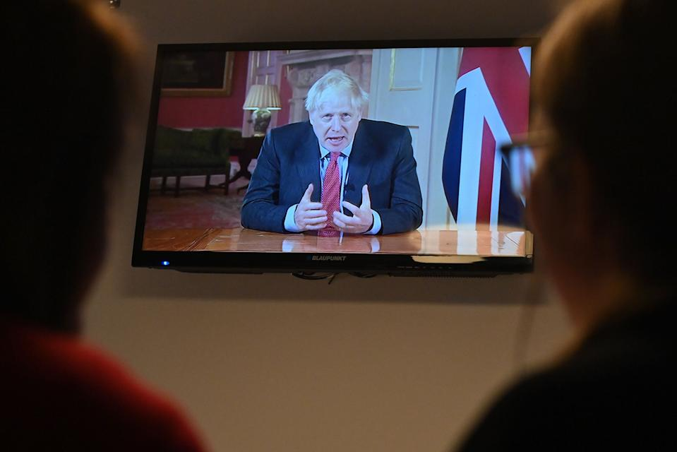 Members of a family watch as Britain's Prime Minister Boris Johnson addresses the nation about the latest updates on the novel coronavirus COVID-19 restrictions, on their television in their home in Liverpool on September 22, 2020. - Britain on Tuesday tightened restrictions to stem a surge of coronavirus cases, ordering pubs to close early and advising people go back to working from home to prevent a second national lockdown. (Photo by Paul ELLIS / AFP) (Photo by PAUL ELLIS/AFP via Getty Images)