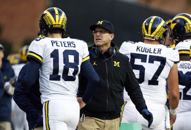 Michigan head coach Jim Harbaugh, center, speaks with quarterback Brandon Peters in the first half of an NCAA college football game against Maryland in College Park, Md., Saturday, Nov. 11, 2017. (AP Photo/Patrick Semansky)