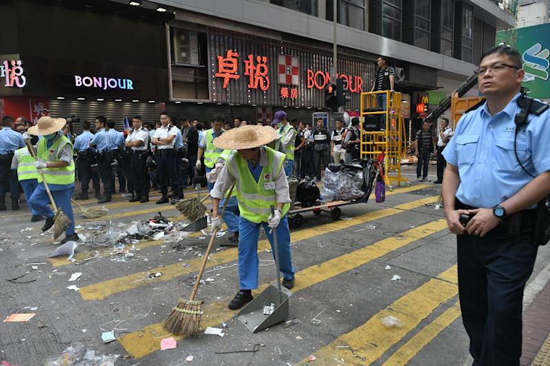 Police stand by as workers clean a road previously occupied by pro-democracy protesters in the Mongkok district of Hong Kong, on November 26, 2014