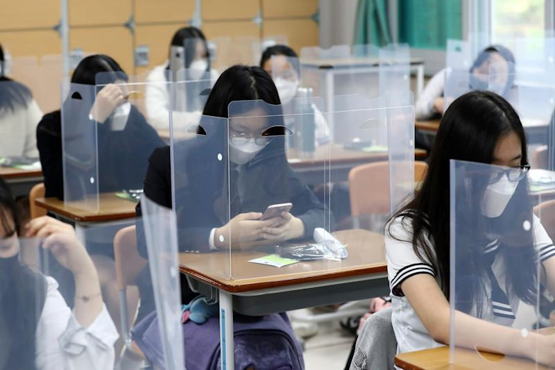 Senior students wait for class to begin with plastic boards placed on their desks at Jeonmin High School in Daejeon, South Korea. Hundreds of schools have since had to close after a spike in cases: AP