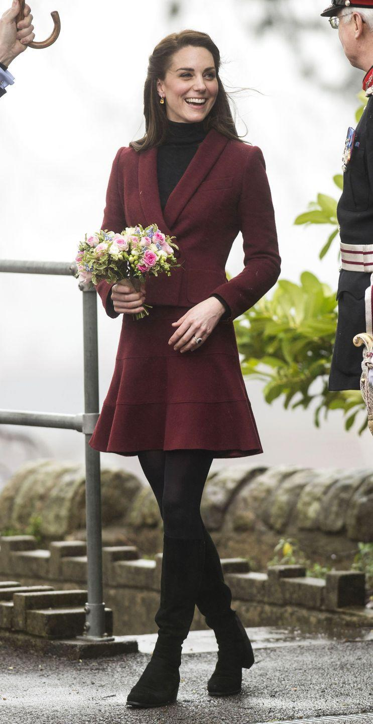 <p>The Duchess of Cambridge wears a maroon Paule Ka skirt suit, black tights, gloves and knee-high boots by Stuart Weitzman during a visit to Wales.</p>