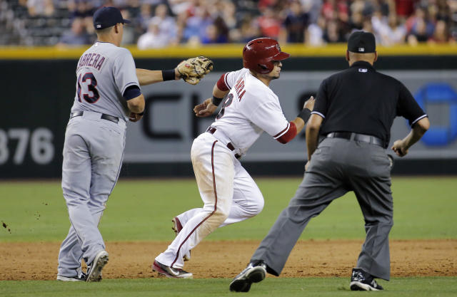 Arizona Diamondbacks' Gerardo Parra eludes the tag of Cleveland Indians' Asdrubal Caabrera (13) as umpire Vic Carapazza watches during the sixth inning of a baseball game, Tuesday, June 24, 2014, in Phoenix. Parra was ruled safe after avoiding the tag in a rundown. (AP Photo/Matt York)