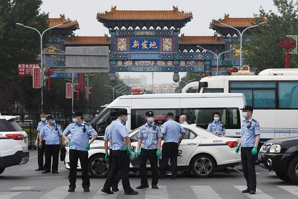 Chinese police guard the entrance to the closed Xinfadi market in Beijing.