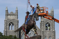 FILE - In this July 7, 2020, file photo, crews attach straps to the statue Confederate General J.E.B. Stuart on Monument Avenue in Richmond, Va. At least 160 Confederate symbols were taken down or moved from public spaces in 2020. That's according to a new count the Southern Poverty Law Center shared with The Associated Press. (AP Photo/Steve Helber, File)